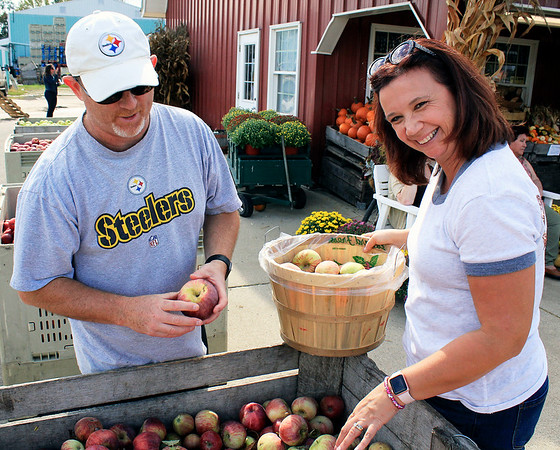 Roger Schneider | The Goshen News<br /> Elkhart residents Tory and Lisa Hyson select some apples Saturday at Kercher's Sunrise Orchard and Farm Market in Goshen.
