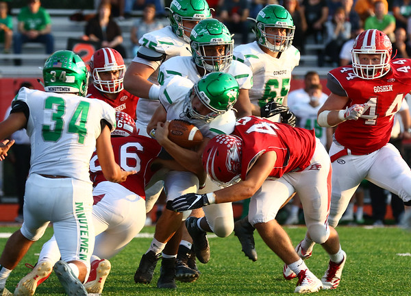 JAY YOUNG | THE GOSHEN NEWS<br /> Concord High School senior running back Jack Lietzan, center, is brought down by Goshen High School defenders Drew Marlow (26) and Will Koshmider (49) during their game Friday night at GHS.
