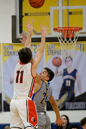 BEN MIKESELL | THE GOSHEN NEWS<br /> Goshen senior Will Line attempts a three-point shot over East Noble sophomore Hayden Jones during Thursday's game in the 2017 Fairfield Holiday Tournament.