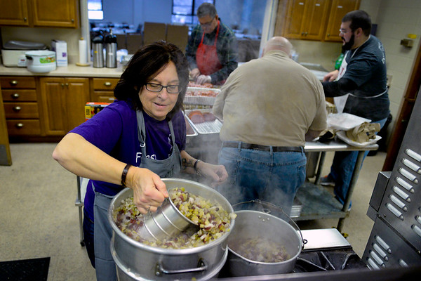 BEN MIKESELL | THE GOSHEN NEWS<br /> Susie Hooley, coordinator for the Christmas dinner, prepares a mixture of celery, cranberries and onions for stuffing Saturday at First Presbyterian Church. Hooley expected to serve nearly 800 guests Monday.
