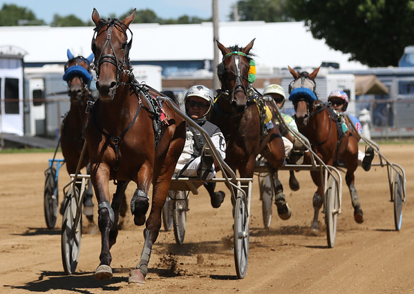 JAY YOUNG | THE GOSHEN NEWS<br /> Don Eash leads a pack of racers to the finish line during the sixth race Tuesday morning on the final day of harness racing at the Elkhart County 4-H Fair.