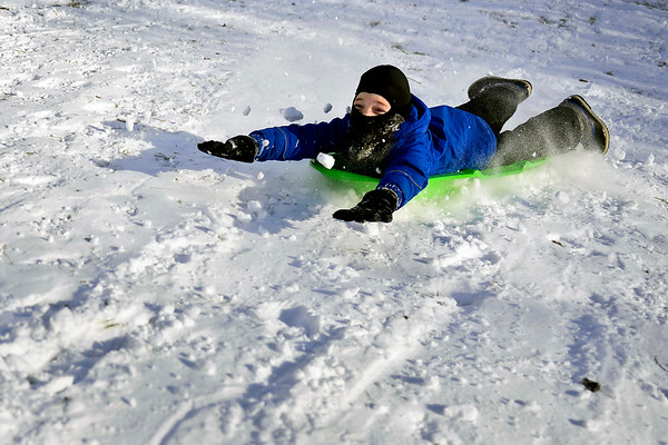 BEN MIKESELL | THE GOSHEN NEWS<br /> Eleven-year-old Elliot Hertzler Gascho of Goshen barrels down the sledding hill at Abshire Park on Christmas Day in Goshen. In their first sledding trip of the season, he and his brother Simon, 15, took turns speeding down the hill.
