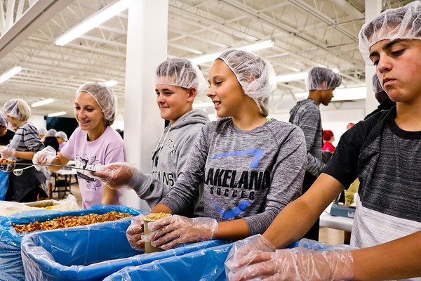 LEANDRA BEABOUT | THE GOSHEN NEWS<br /> Westview High School seniors line up to assemble meals for Feed My Starving Children. From left: Emily Byler, Bryce Alleshouse, Emilee Baczinski and Clinton Bowers.