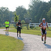 SHERRY VAN ARSDALL | THE GOSHEN NEWS<br /> Runners make thier way around the perimeter of Fidler Pond in the 5K run duirng the third annual triathlon and mile swim in Goshen Saturday.