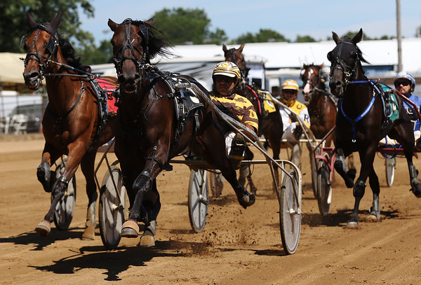 JAY YOUNG | THE GOSHEN NEWS<br /> Doug Rideout leads the pack as they approach the finish line during the fifth race Tuesday morning on the final day of harness racing at the Elkhart County 4-H Fair.
