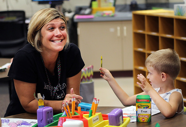 "JULIE CROTHERS BEER | THE GOSHEN NEWS<br /> Donning her ""Kindergarten Rocks!"" T-shirt, Nappanee Elementary School kindergarten teacher Katie Miller smiles at a student in her class while kindergartner Evan Green selects a crayon for his coloring project."