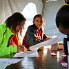 LEANDRA BEABOUT | THE GOSHEN NEWS<br /> Volunteers Sherry Wenger and Annika Smith help walkers register for the Saturday Maple City Walk.