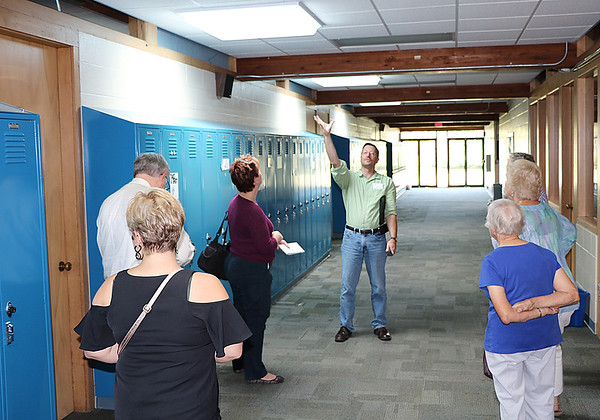 JOHN KLINE | THE GOSHEN NEWS<br /> Calvin Swartzendruber, a chemistry and physics teacher at Bethany Christian Schools, center, points to one of the school's many skylights during a tour of the school's sustainability efforts Friday afternoon.