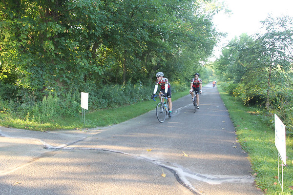 SHEILA SELMAN | THE GOSHEN NEWS<br /> John Martin, front, and his son, Andy Martin, Granger, pull in at the Abshire Park SAG during their 40-mile venture on the Quilt Gardens Ride Saturday morning.