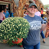 Roger Schneider | The Goshen News<br /> Sara Jennings of Elkart purchased some mums and colorful corn Saturday at Kercher's Sunrise Orchard and Farm Market in Goshen.