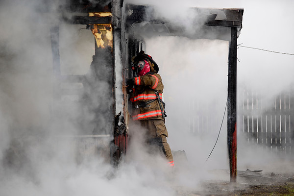 BEN MIKESELL | THE GOSHEN NEWS<br /> A fire figher from the Benton Township Fire Department pries wood from a house on fire Tuesday morning at the 16000 block of C.R. 40 in Goshen. Passersby called the authorities and helped the residents out of the house, who were sleeping when the fire started.