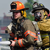 BEN MIKESELL | THE GOSHEN NEWS<br /> Middlebury fire fighter Neil Miller, left, and Clinton fire fighter Kendrick Yoder, right, spray water on a house fire at 11230 C.R. 34 east of Goshen Tuesday morning.