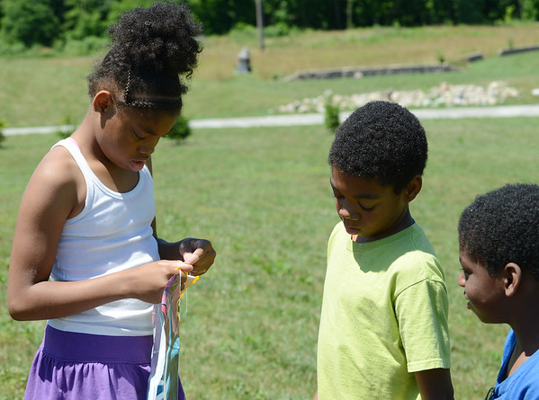 HALEY WARD | THE GOSHEN NEWS<br /> Siblings Jay'Brianna Stokes, Jay'Briel Stokes and Jay'Vonte Bryant fix a kite they found on Monday at Allan J. Kauffman Park.