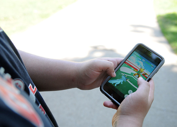 HALEY WARD | THE GOSHEN NEWS <br /> Tobias Garcia, 16, Goshen, battles to take over the gym at the Elkhart County Courthouse while playing Pokémon Go on Thursday.