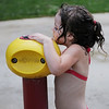 HALEY WARD | THE GOSHEN NEWS <br /> Aamaya Tackett, 3, presses the button to get more water at the splash pad on Thursday at Walnut Park.