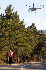 Scott Frazier walks towards his car while a wildfire helicopter passes overhead on Friday, Sept. 17, during the Peewink Fire west of Boulder. Jeremy Papasso/ Camera
