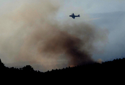 PEEWINK A slurry bomber flies over the Peewink Fire on Friday evening. Photo by Marty Caivano/Camera/Sept. 17, 2010