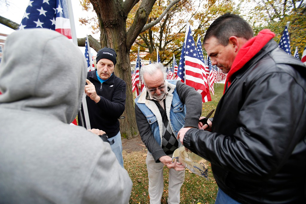 . Real Gadoury, center, the president of the Pittsfield Kiwanis Club, organizes volunteers as they install the hundreds of flags for the annual Park of Honor event at Park Square. The flags each represent donations toward a scholarship fund for children of Berkshire County veterans and will remain at the park through the end of November. Saturday, October 29, 2016. Stephanie Zollshan � The Berkshire Eagle | photos.berkshireeagle.com