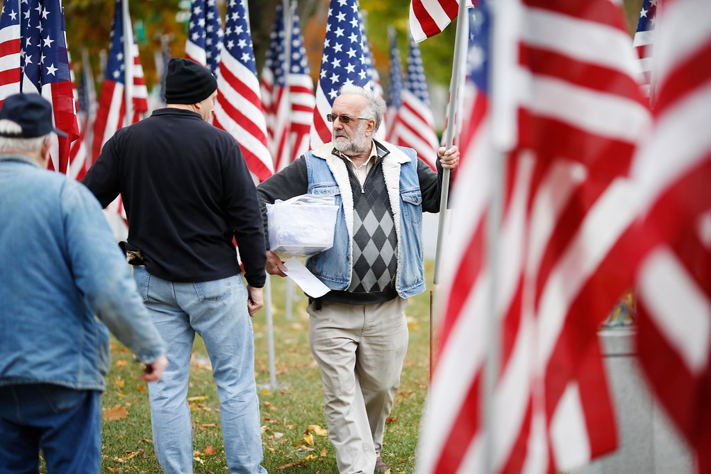. Real Gadoury, the president of the Pittsfield Kiwanis Club, organizes volunteers as they install the hundreds of flags for the annual Park of Honor event at Park Square. The flags each represent donations toward a scholarship fund for children of Berkshire County veterans. Saturday, October 29, 2016. Stephanie Zollshan � The Berkshire Eagle | photos.berkshireeagle.com