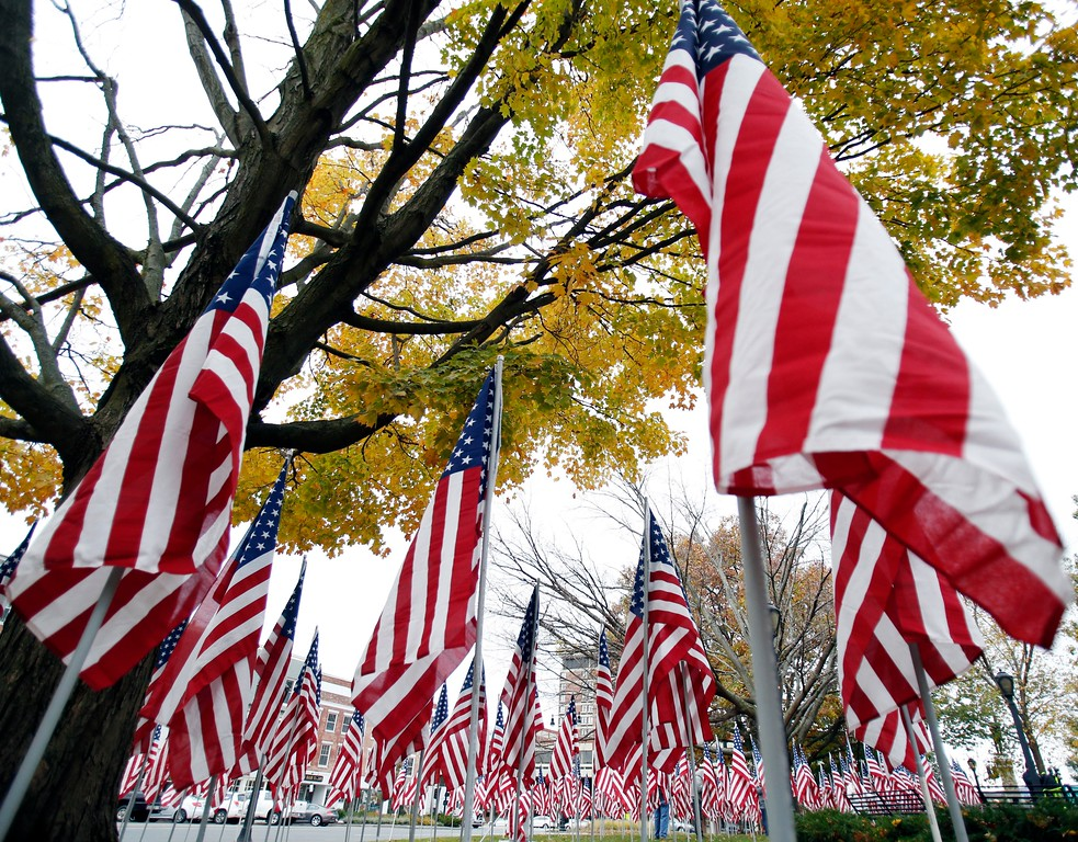 . Volunteers install the hundreds of flags for the annual Park of Honor event at Park Square. The flags each represent donations toward a scholarship fund for children of Berkshire County veterans and will remain on the park through the month of November. Saturday, October 29, 2016. Stephanie Zollshan � The Berkshire Eagle | photos.berkshireeagle.com