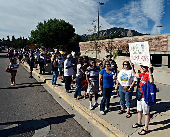 """Vicki Denhoffer, of Aurora, holds a sign for the group Autism Speaks while waiting in line to hear President Barack Obama speak on Norlin Quad at the University of Colorado in Boulder on Sunday, Sept. 2, 2012.  For more photos and videos visit  <a href=""""http://www.DailyCamera.com"""">http://www.DailyCamera.com</a>.<br /> (Greg Lindstrom/Times-Call)"""