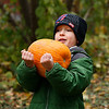 First grader, Patrick Kelley has all hands on deck while carrying his large pumpkin.