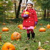 Myla Coyne, a student in Pre - K smiles after finding the perfect pumpkin.