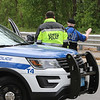 Lowell Police waving a car to slow down Saturday afternoon at the scene of fatality on Pawtucket Boulevard in Lowell near the former MA/COM building, where Jose and Fernanda Medina were killed Thursday evening while walking on the sidewalk by a vehicle that veered off the road. (SUN/Julia Malakie)