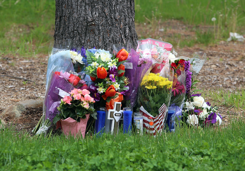 Scene of fatality on Pawtucket Boulevard in Lowell near the former MA/COM building, where Jose and Fernanda Medina were killed while walking on the sidewalk by a vehicle that veered off the road. Flowers at the base of a tree, mostly brought by a group of a dozen family members who came with flowers and spend about half an hour, ending by gathering in a circle for a prayer Saturday afternoon. (SUN/Julia Malakie)