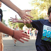 "Santiago Paiva, 7, of Louisville, gets some high-fives from spectators as he approached the finish line in the Kids Race on Thursday, Aug. 11, during the Pearl Street Mile race for the 2011 Run Boulder Series. For more photos of the race go to  <a href=""http://www.dailycamera.com"">http://www.dailycamera.com</a><br /> Jeremy Papasso/ Camera"
