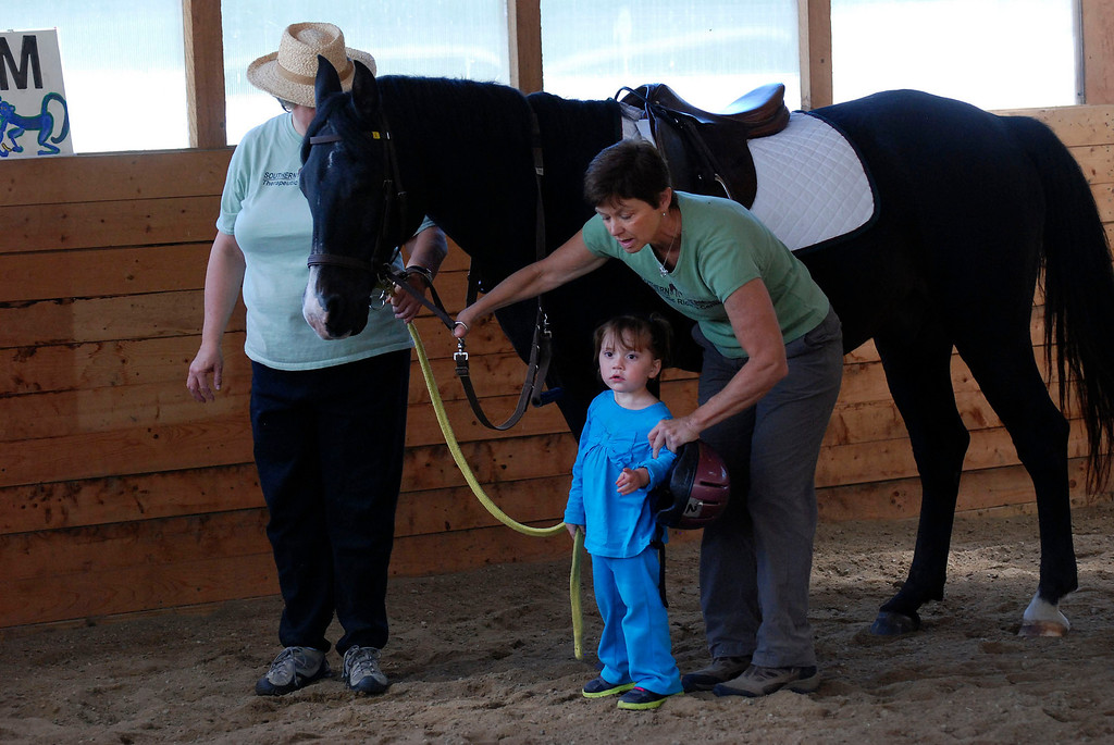 """. Kayla Rice/Reformer                                 Program Director Lorna Young (right) and volunteer Patsy Mehlhop (left) work with the horse \""""Spot\"""" and Lexi Leland, 3, during Lexi\'s weekly horse therapy at Winchester Stables in Newfane."""