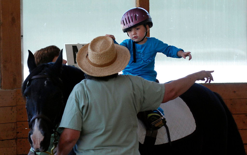 """. Kayla Rice/Reformer                                 Lexi Leland, 3, points with volunteer Patsy Mehlhop while doing exercises on therapy horse \""""Spot\"""" during Lexi\'s weekly horse therapy at Winchester Stables in Newfane."""