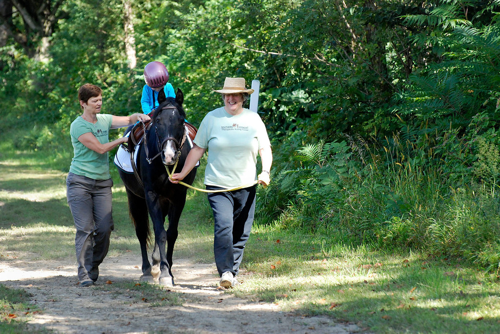 """. Kayla Rice/Reformer                                 Program Director Lorna Young (left) and volunteer Patsy Mehlhop (right) guide the horse \""""Spot\"""" and rider Lexi Leland, 3, during Lexi\'s weekly horse therapy at Winchester Stables in Newfane."""