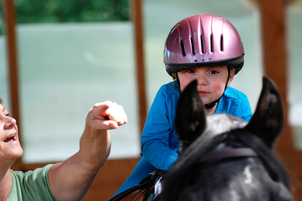 . Kayla Rice/Reformer                                 Program Director Lorna Young (left) works with Lexi Leland, 3, during Lexi\'s weekly horse therapy at Winchester Stables in Newfane.