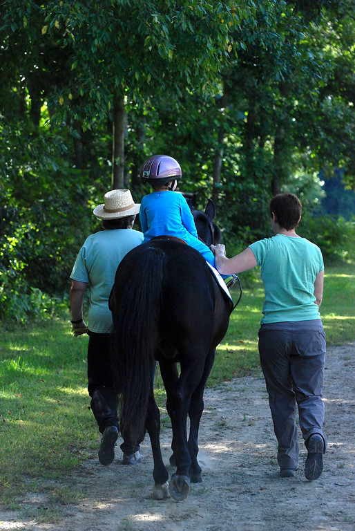 """. Kayla Rice/Reformer                                 Program Director Lorna Young (right) and volunteer Patsy Mehlhop (left) guide the horse \""""Spot\"""" and rider Lexi Leland, 3, during Lexi\'s weekly horse therapy at Winchester Stables in Newfane."""