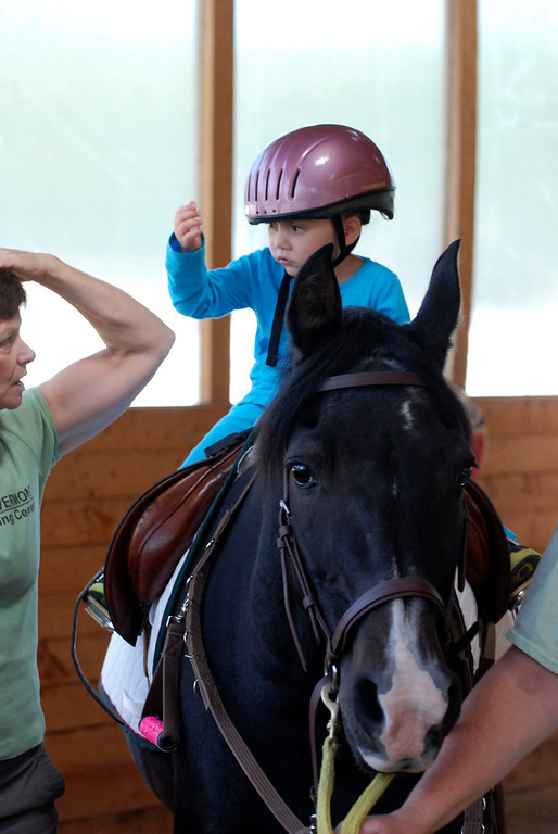 """. Kayla Rice/Reformer                                 Program Director Lorna Young (left) works with Lexi Leland, 3, on a horse named \""""Spot\"""" during Lexi\'s weekly horse therapy at Winchester Stables in Newfane."""