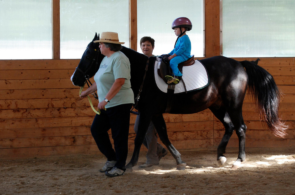 """. Kayla Rice/Reformer                                 Program Director Lorna Young and volunteer Patsy Mehlhop (left) guide the horse \""""Spot\"""" and rider Lexi Leland, 3, during Lexi\'s weekly horse therapy at Winchester Stables in Newfane."""