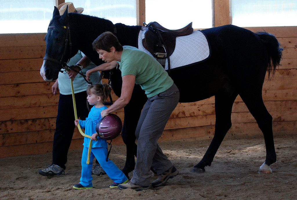 """. Kayla Rice/Reformer                                 Program Director Lorna Young (right) and volunteer Patsy Mehlhop help Lexi Leland, 3, guide therapy horse \""""Spot\"""" during Lexi\'s weekly horse therapy at Winchester Stables in Newfane."""