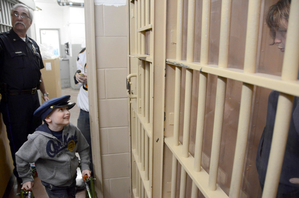 . Brayton Elementary School first grader Zach Hillard, 7, who has cerebral palsy, had his wish come true on Tuesday, April, 29, 2014. Hillard, who is undergoing major surgery in June, got the chance to spend the morning with North Adams Police Officer Mark Bailey, ride in a police cruiser, arrest his mother, tour the police and fire departments, meet the Mayor, and ride in a North Adams Fire Department truck. Zach looks in at his mother who is in a jail cell. Gillian Jones / Berkshire Eagle Staff / photos.berkshireeagle.com