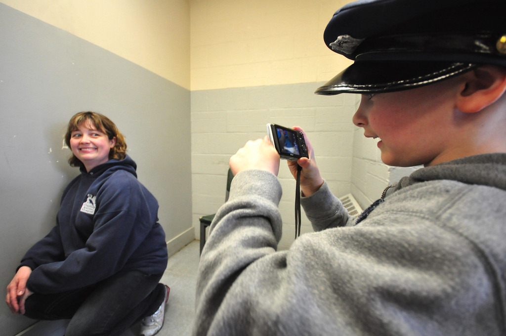 . Brayton Elementary School first grader Zach Hillard, 7, photographs his mother, Dr. Heather Blake, as she is \'booked\' at the North Adams Police Department, following being \'arrested\' from their State Road home in North Adams on Tuesday, April, 29, 2014. Gillian Jones / Berkshire Eagle Staff / photos.berkshireeagle.com