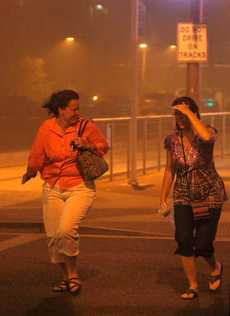 Phoenix Dust Storm.JPEG-0a0.JPG   Mary Nichols and JoAnn Buckson, right, run for cover in Phoenix Tuesday July 5, 2011 as a dust storm blows through.  A massive dust storm has swept into the Phoenix area and drastically reduced visibility across much of the valley. (AP Photo/DAVID KADLUBOWSKI  / Arizona Republic) NO SALES