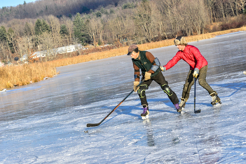 KRISTOPHER RADDER — BRATTLEBORO REFORMER<br /> Richard Forye tries to keep the puck away from Eric Slayton during a pick-up ice hockey game at the Retreat Meadows on Wednesday, Dec. 12, 2018.