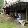 A visitor takes a break to have some ice cream in the shade of a horse corral Saturday. Photo by Pat Christman