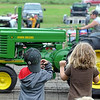 A pair of children watch a tractor during the antique tractor pull Saturday. Photo by Pat Christman