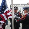 Pittsfield Police Officer Miles Barber, flanked by retired Officer Raymond Bush, left, and retired Detective Richard LeClair, right, prepare to raise the American flag during Monday's Police Memorial Day ceremony outside of the Pittsfield Police Station.