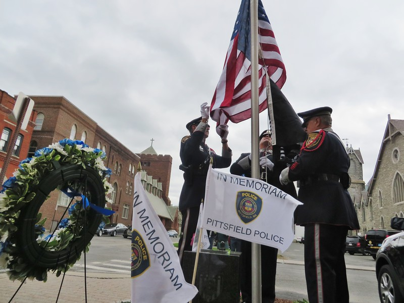 From left: Pittsfield Police Department Honor Guard members, retired Officer Raymond Bush, Officer Miles Barber, and retired Detective Richard LeClair, raise the American flag to half staff tribute to law enforcement members who died in service. This week marks National Police Week, a week of remembrance.