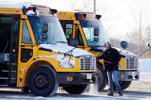 BEN GARVER — THE BERKSHIRE EAGLE<br /> Snow is brushed off a bus in the Pittsfield school bus fleet before the bus is readied for service.