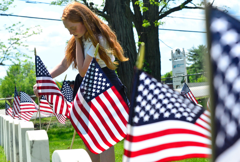 KRISTOPHER RADDER - BRATTLEBORO REFORMER<br /> Ava Cutler, a 7th-grader at St. Michael School, places American fags next the tombstones of military veterans at Locust Ridge Cemetery, on Black Mountain Road, on Wednesday, May 23, 2018.