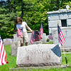 KRISTOPHER RADDER - BRATTLEBORO REFORMER<br /> Regina Patria, an 8th-grader at St. Michael School,  knees down to place an American Flag next to a tombstone at St. Michael's cemetery, on White Birch Avenue, on Wednesday, May 23, 2018.