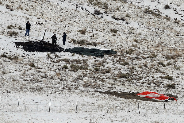 Investigators look over the tail section of the Cirrus SR20 on Sunday afternoon.<br /> At least three people died Saturday afternoon after two planes, one of them pulling a glider, collided in north Boulder, scattering debris over 115 acres of open space.<br /> Cliff Grassmick / February 7, 2010